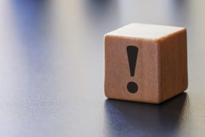 Warning exclamation mark on a wooden block